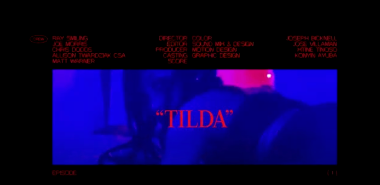 """Image shows a dimly lit photo of a black woman clad in black lingerie, the word """"TILDA"""" is placed over her photo with credits of the crew atop."""
