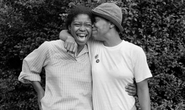 Two black lesbians from the 1970s hold each other while laughing and smiling for the camera in this black and white photo. One of them is in a button down shirt with rolled up sleeves and their hair in a bun. The other one is in a white tee and a hat.
