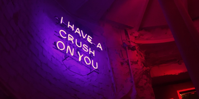 """A bright purple sign says """"I have a crush on you"""" in Neon lights against a black brick wall with red accents."""