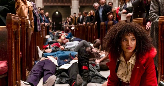 "In a still from the television show Pose, Indya Moore sits on the floor of St. Peter's Cathedral during a staged ""die in"" during the early 1990s of HIV/AIDS Activism"