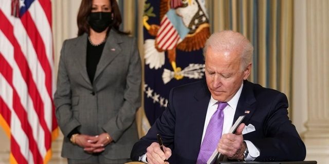 President Joe Biden signs papers in the White House with Vice President Kamala Harris in the background.
