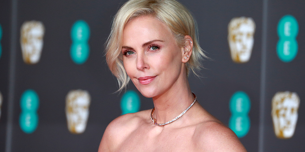 Charlize Theron walks a red carpet in London.