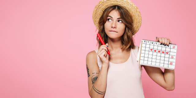 A tattooed woman with brown hair in a straw hat stands in front of a pink background. She holds a red pen and a calendar that has some days marked with red hearts.