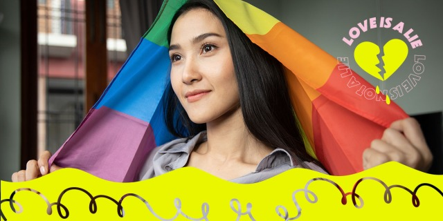 A person stands with a rainbow flag draped over their head, staring off into the middle distance.