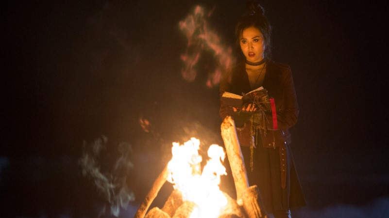 nico stands in front of a fire in runaways