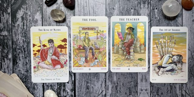Four tarot cards from the Next World deck arranged on a wooden surface surrounded by some stones and crystals; from left to right, the cards are the King of Wands, the Fool, the Teacher and the Ten of Swords.