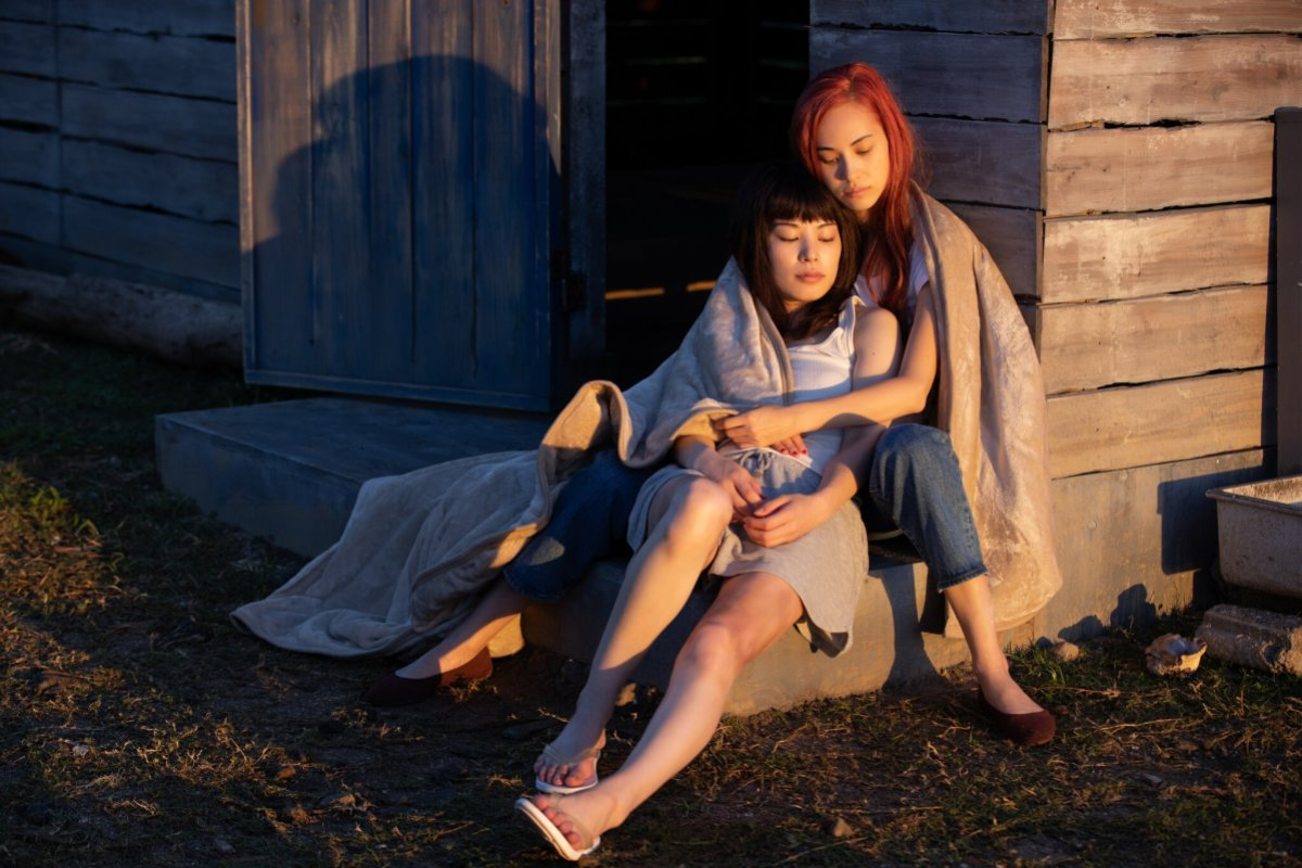 """Two women holding each other sitting outside a house at sunset, still from """"Ride or Die"""""""