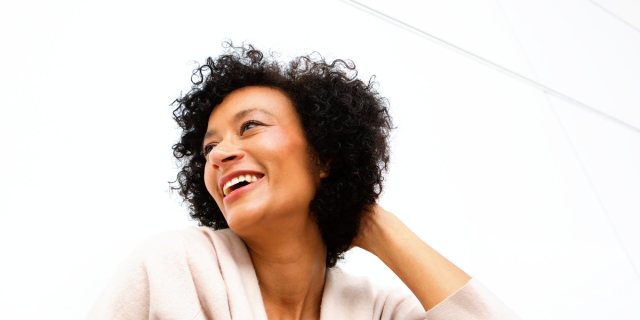 An older woman with short curly hair looks to the side, laughing at something out of frame
