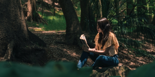 someone with long hair reading in a forest
