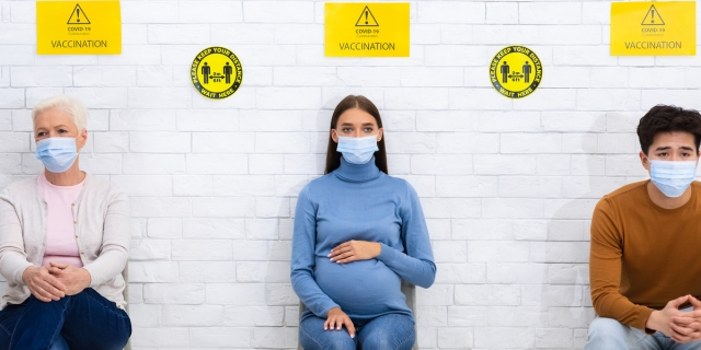 Three people sit in socially distanced chairs, wearing masks as signs above their heads indicate they're in line to receive the COVID-19 vaccine.