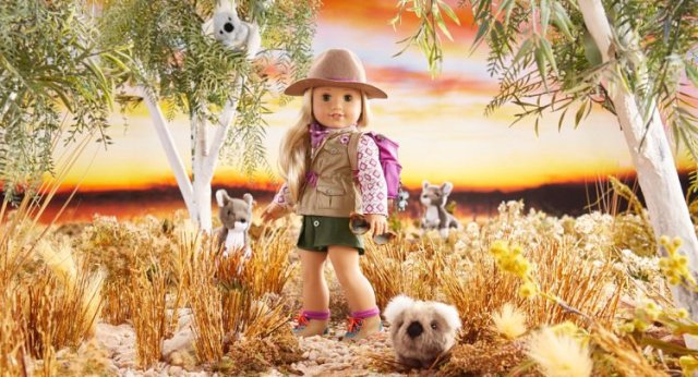 A blonde American Girl doll is posed as if she is hiking with Koalas in Australia. She has on a pink backpack.