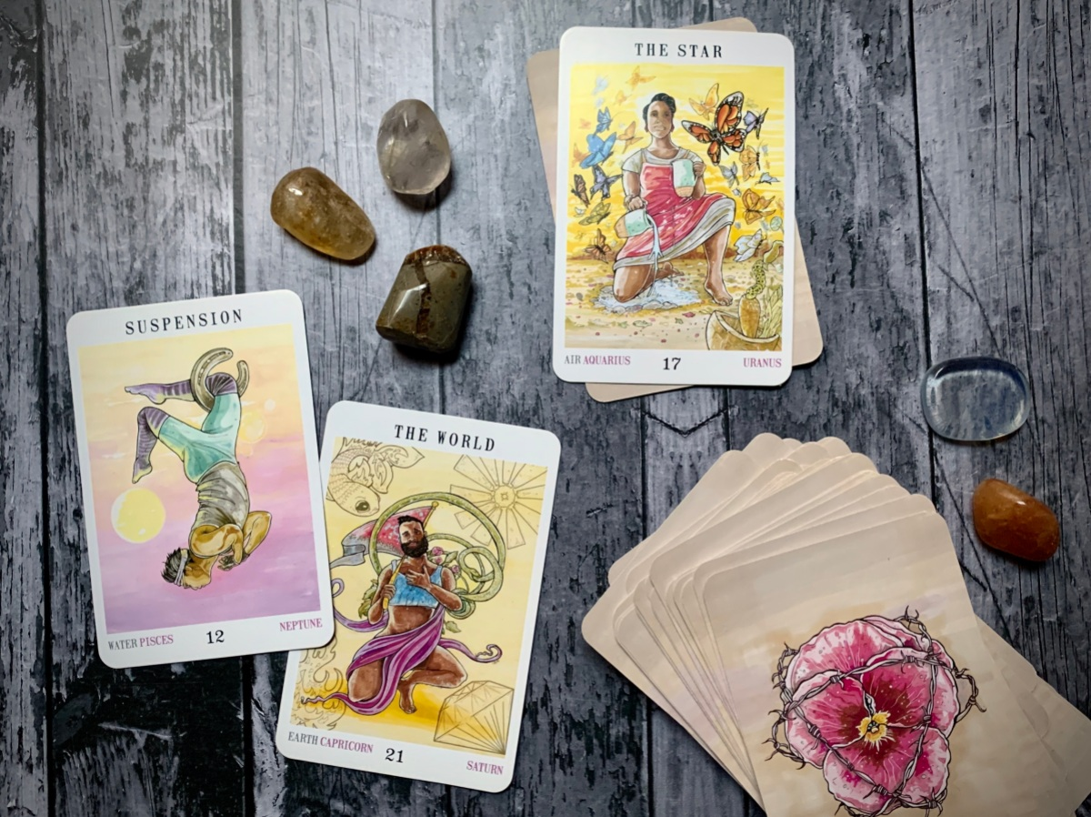 The Star card, the Suspension card, and the World card from the Next World tarot deck upturned on a wooden backdrop with a number of stones and crystals.
