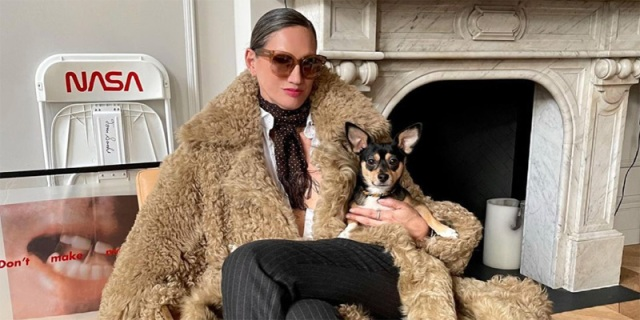 Style Maven Jenna Lyons relaxes in a full length faux fur coat and her hair slicked back in a bun and dark cateye sunglasses. She is holding a small dog in her arms and is in front of a fire place. She's a boss, personified.