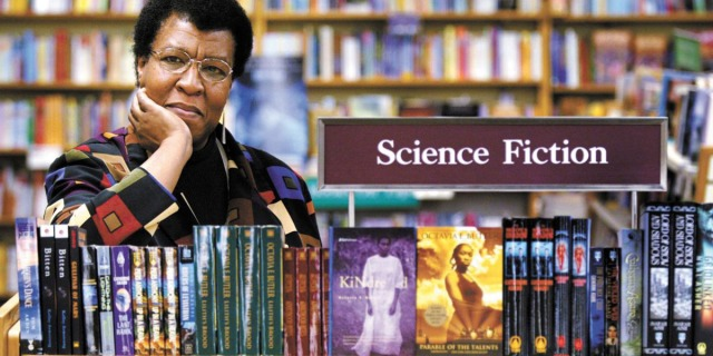 """Octavia Butler in the 1990s stands in front of a collection of her books under the sign """"Science Fiction"""" in a library"""