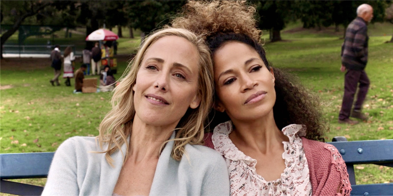 Dr. Teddy Altman sits on a bench with her ex-girlfriend in Central Park. The bench is blue, the grass is green, and the girlfriends rest their heads on each other's shoulders in love.