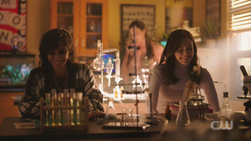 Scene from Legacies: Finch and Josie laugh and smile while sitting at a high school science lab table together.