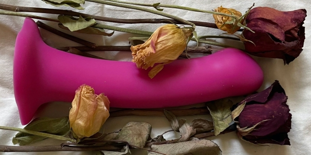 a purple dildo lies in a bouquet of dead roses