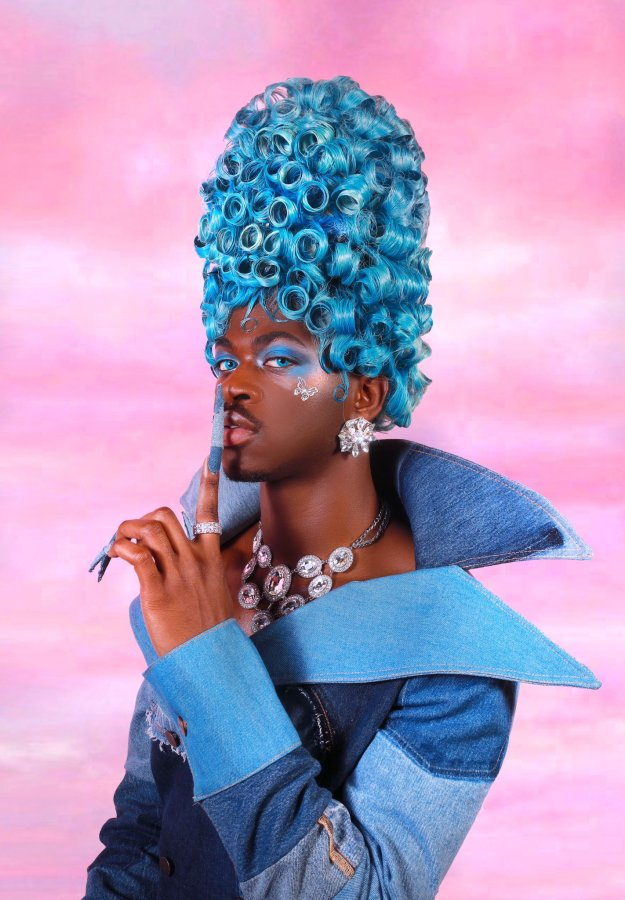Lil Nas X queer promo Image shows Lil Nas X in a denim outfit with blue coiled hair stacked to the top. Long acrylic nails and clad in a diamond necklace and large diamond earrings. A cloudy pink background is behind them.