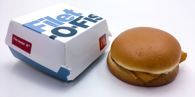 A McDonald's Filet-O-Fish sandwich sits net to a cardboard sandwich box.