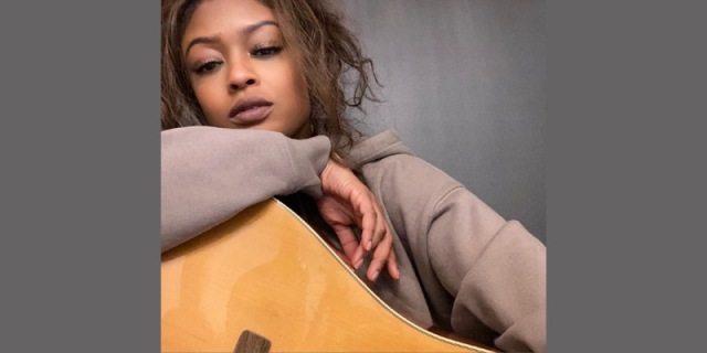 Actress Javicia Leslie is in a taupe brown sweatshirt with her her hair in a loose curly ponytail. She is holding a guitar and looking at the camera with her eyes low.