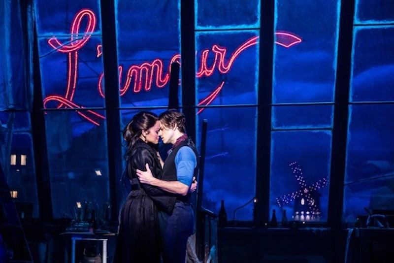"In a still form the play Moulin Rouge two actors hold each other in an embrace against windows that shine the word ""L'amour"" in red neon."