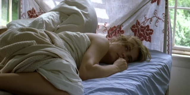 A still from High Art. Syd lies in bed with disheveled covers.