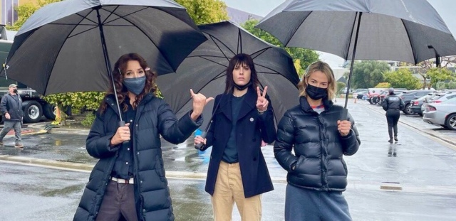 Jennifer Beals, Kate Moennig and Leisha Hailey wearing masks in the rain with umbrellas