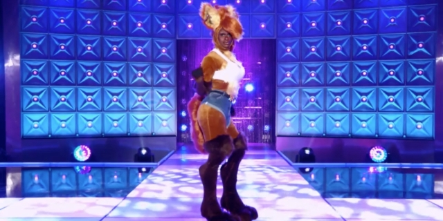 Symone is on the Drag Race runway in a fox costume with tiny denim shorts and white tank top