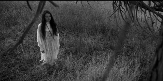"""A still of a moment from Jayli Wolf's """"Child of the Government"""" video, in which the artist stands facing a tree in a field wearing a flowing white nightgown."""