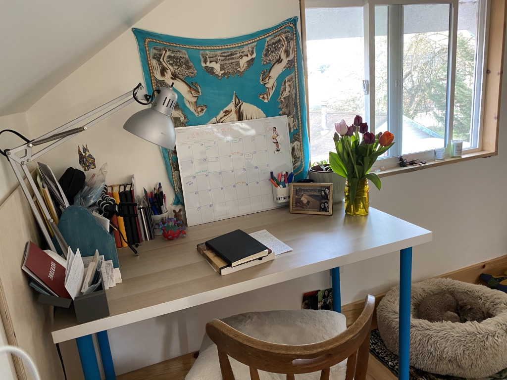 Camila's well-organized desk featuring a vase of flowers, a large calendar, multiple notebooks, and a dog bed beside it