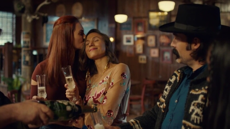 Nicole Haught gently kisses a smiling Waverly Earp's temple as they stand in Shorty's, Waverly with a champagne flute in her hand.