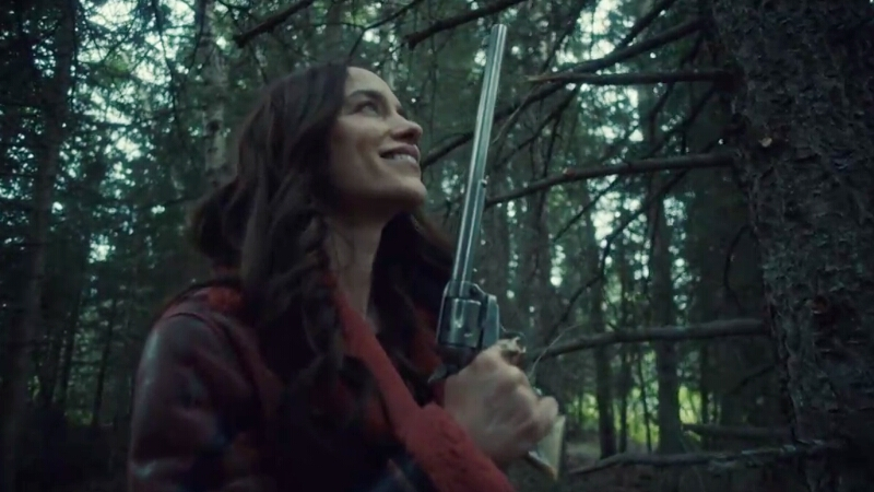 Wynonna Earp stands in the woods, smiling a sultry smile at Peacemaker, her trusty buntline special.