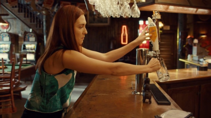 Nicole reaches across the bar to sneak beer from the tap.