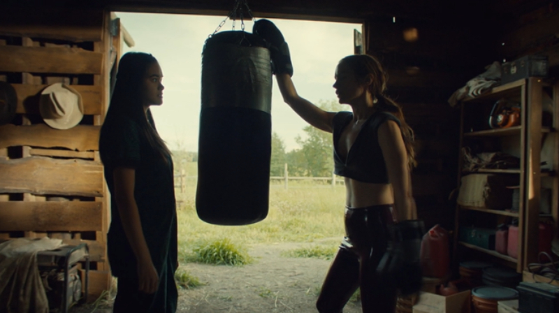Rachel and Wynonna chat with a punching bag between them.