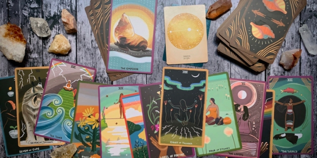 A colorful spread of tarot cards over a wooden surface, with crystals scattered throughout