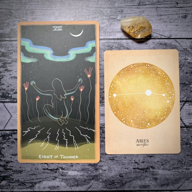 A photo of the tarot card for Eight of Thunder and the astrological card representing Aries, along with a small crystal