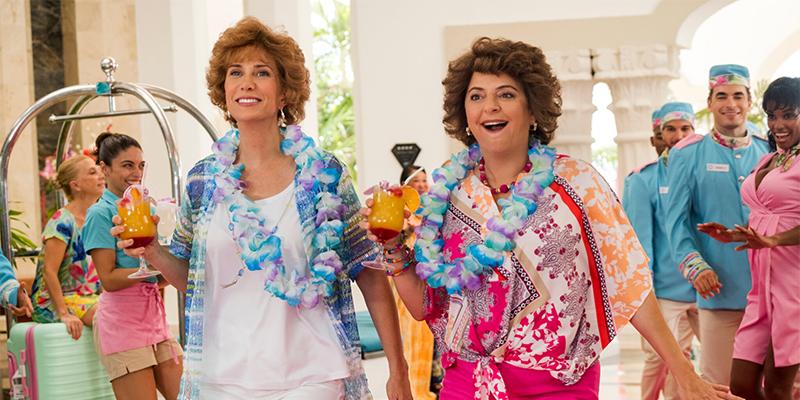 Annie Mumolo and Kristin Wiig walk through a bright hotel lobby holding frozen cocktails.