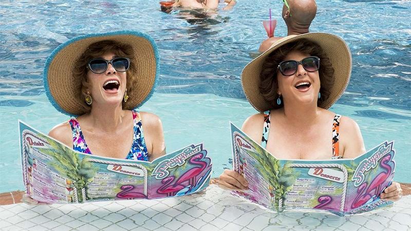 Annie Mumolo and Kristin Wiig wear giant visors in a hotel pool.