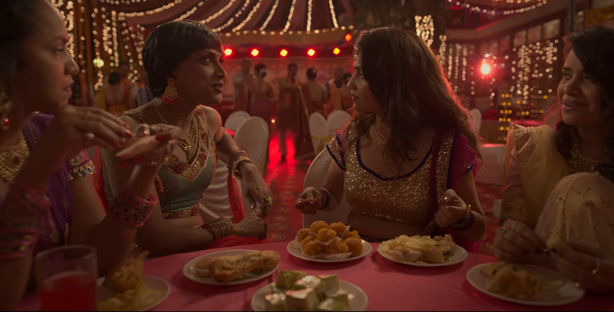 Bombay Begums queer storyline: Lily's friends are dressed in traditional Indian clothes and sit around a table full of sweets. Lily's friend Beauty is smiling and talking to Lily. Lily is surprised by Beauty's question.
