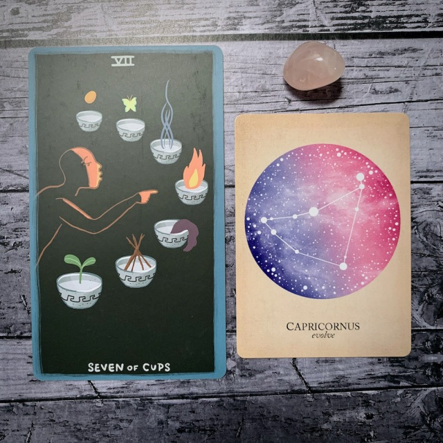 A photo of the tarot card for Seven of Cups and the astrological card representing Capricorn, along with a small crystal