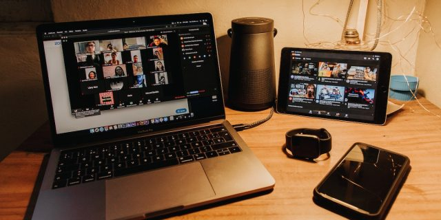 A photo of a laptop on a desk in a dark room lit by a desk lamp, with a highly populated Zoom call on the screen and a range of other electronics, a phone, apple watch and tablet, also running behind it on the same surface