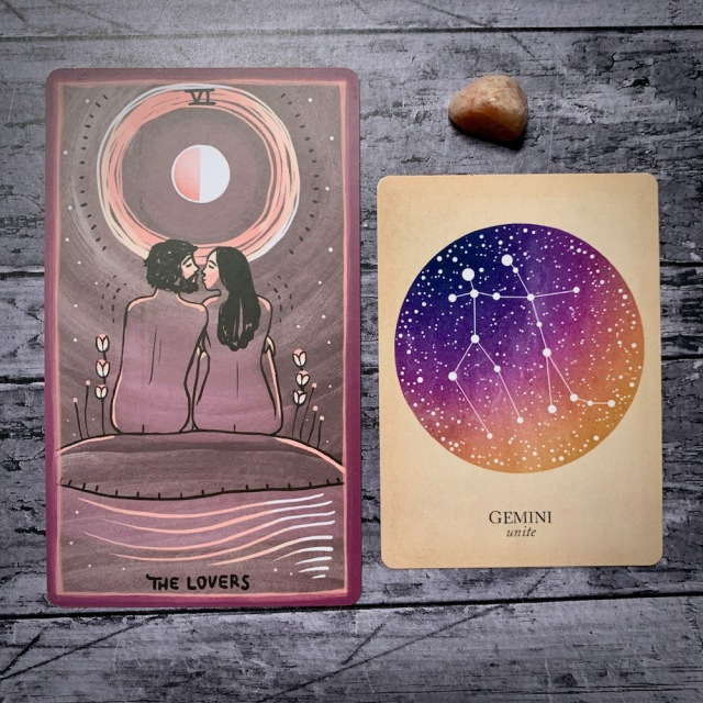 A photo of the tarot card for The Lovers and the astrological card representing Gemini, along with a small crystal