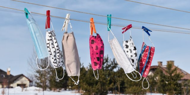 A photo of a series of colorful cloth face masks pinned to a clothesline against a background of trees in the distance and a blue sky