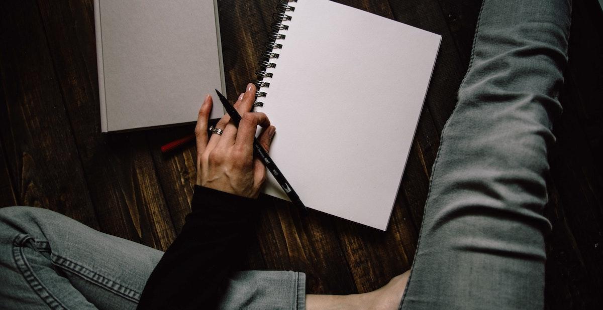 une personne est assise avec une jambe croisée et l'autre tendue et un bloc de papier et un cahier sur le sol devant eux, un stylo en équilibre comme s'il était sur le point d'écrire ou de dessiner