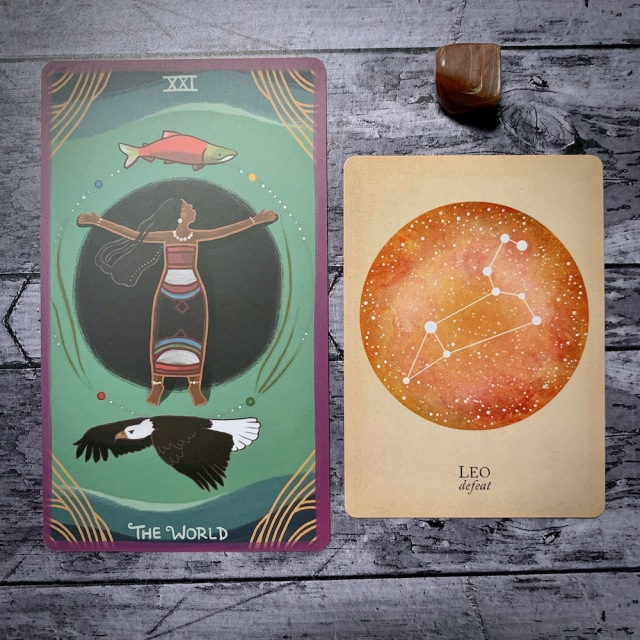 A photo of the tarot card for The World and the astrological card representing Leo, along with a small crystal