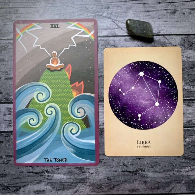 A photo of the tarot card for The Tower and the astrological card representing Libra, along with a small crystal