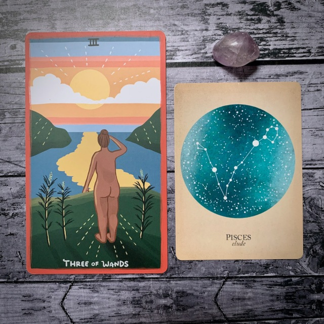 A photo of the tarot card for Three of Wands and the astrological card representing Pisces, along with a small crystal
