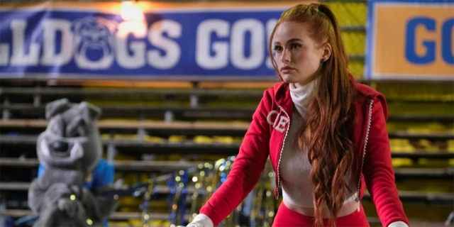 Cheryl Blossom stands on the sidelines of a Riverdale football game in her cheerleading coaching gear.