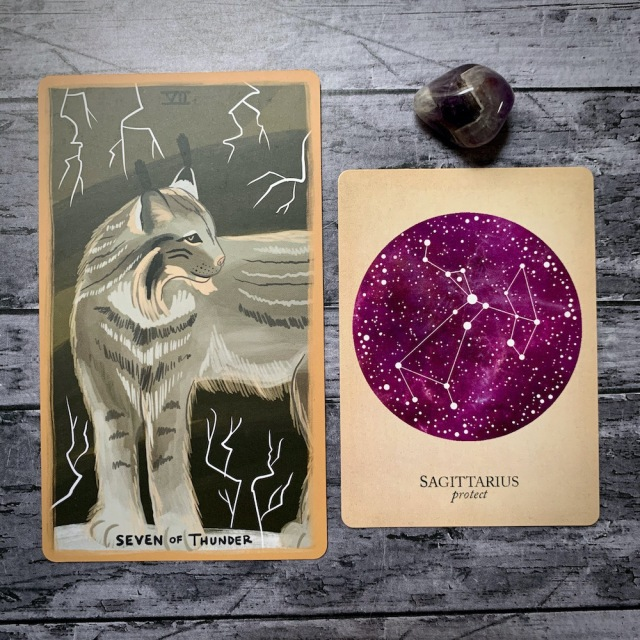 A photo of the tarot card for Seven of Thunder and the astrological card representing Sagittarius, along with a small crystal