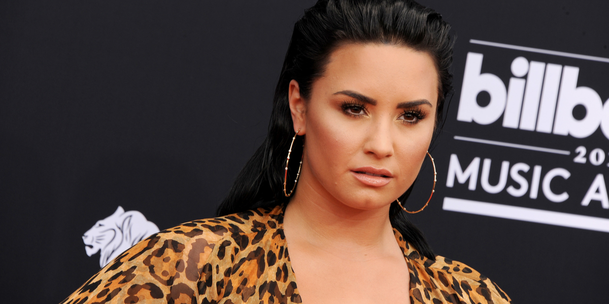 Demi Lovato is pansexual on the red carpet in a leopard print dress and large hoop earrings.